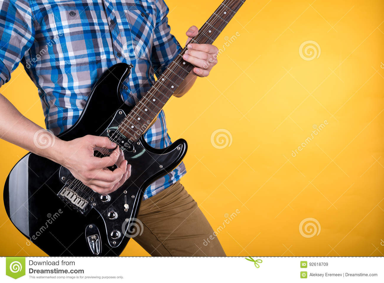 Music And Art. The Guitarist Plays The Electric Guitar On A Yellow ...