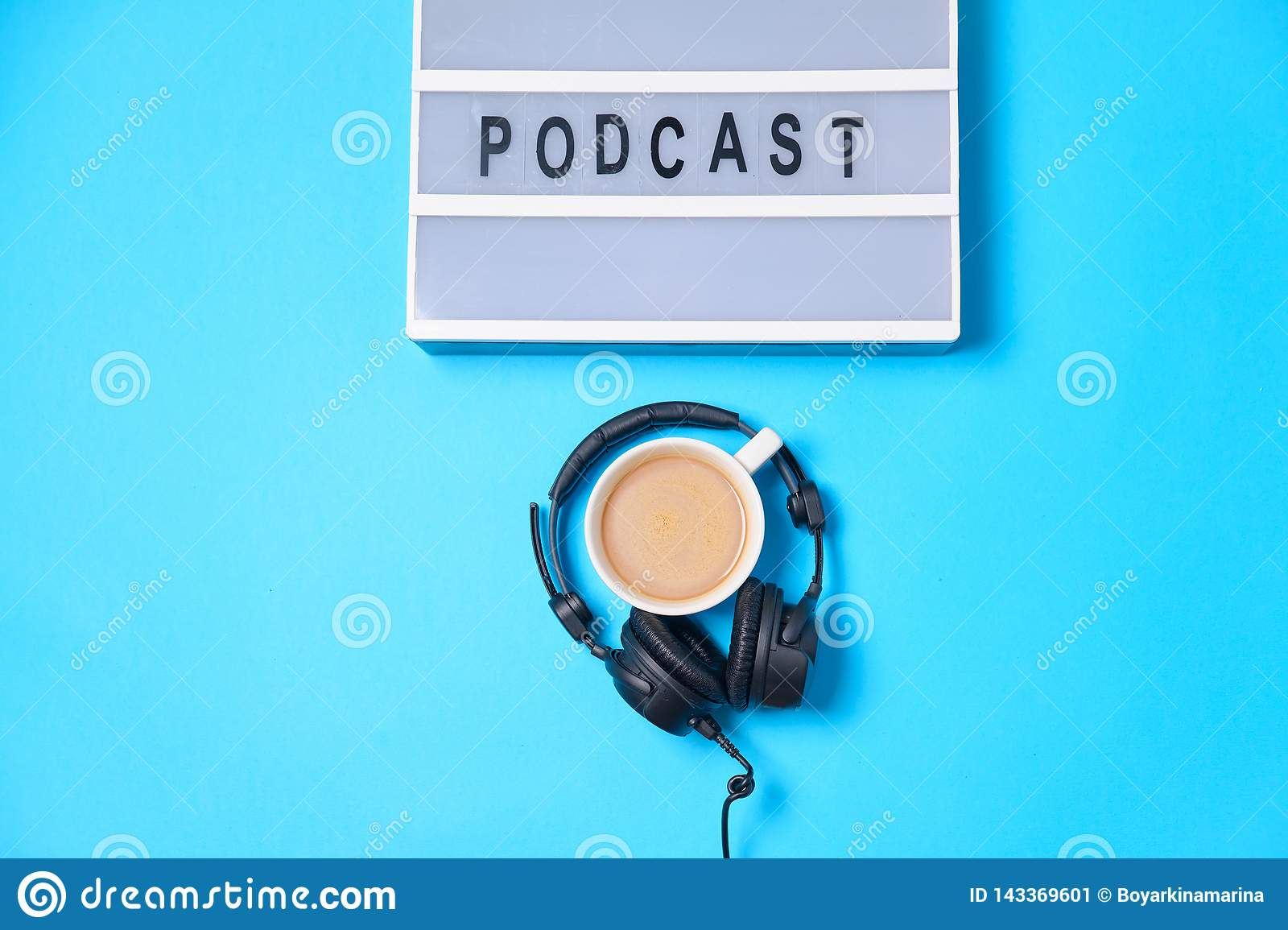 Music background with Podcast word on lightbox, headphones and cup of coffee on blue table, flat lay. Top view, flat lay, space