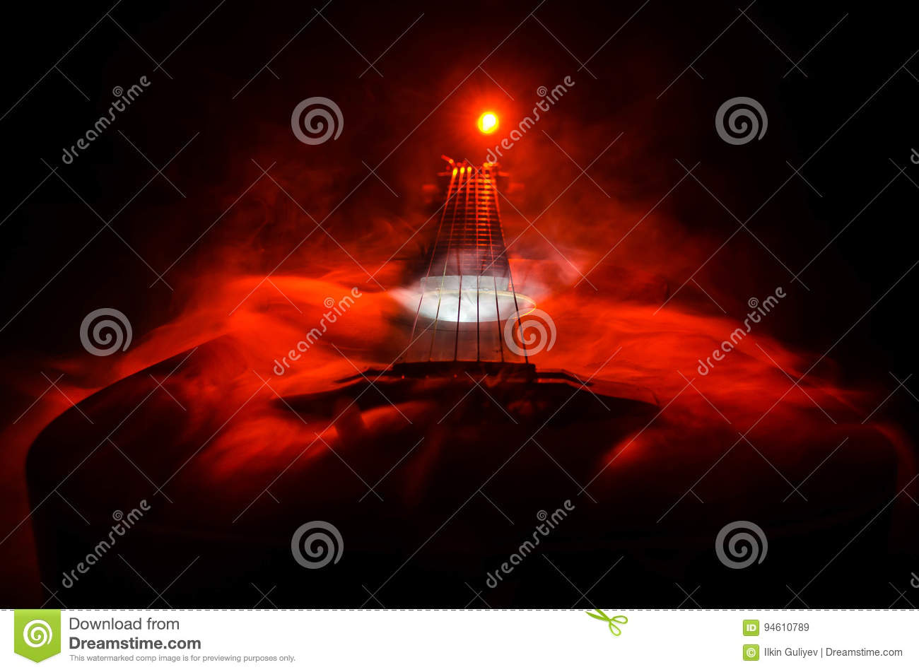 Music concept. Acoustic guitar isolated on a dark background under beam of light with smoke with copy space. Guitar Strings, close