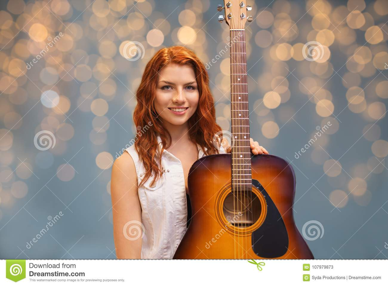 Female Musician With Guitar Over Lights Background Stock Image