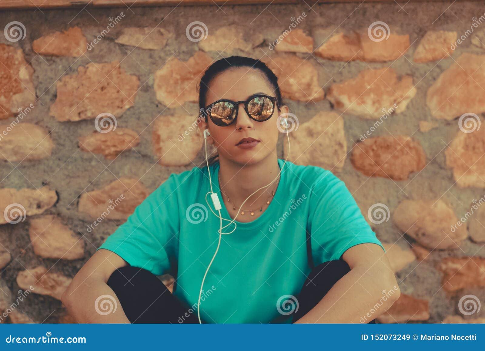 Musica di seduta e d ascolto della giovane bella ragazza dopo il funzionamento