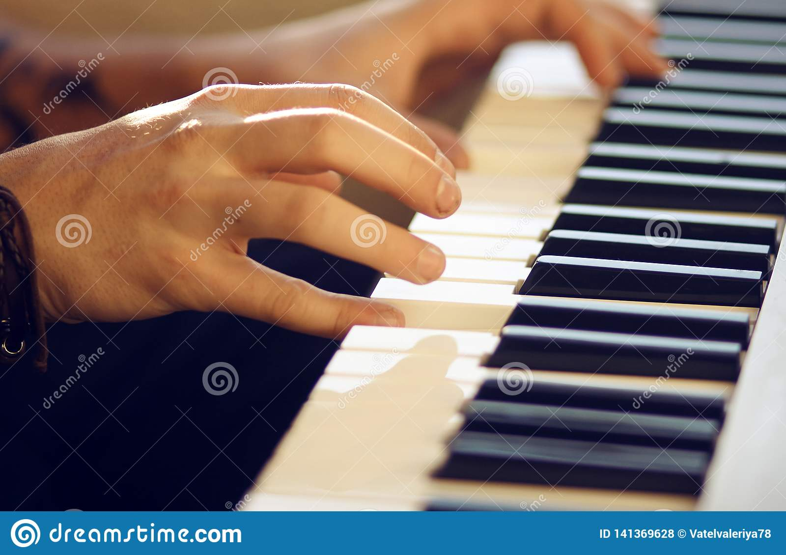 On a musical keyboard instrument man plays a melody with his hands