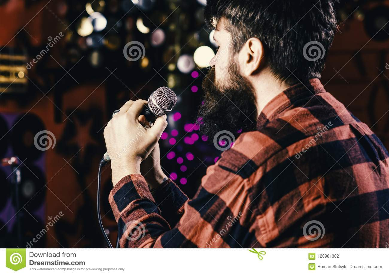 Musician with beard singing song in karaoke, rear view. Man in checkered shirt holds microphone, singing song, karaoke