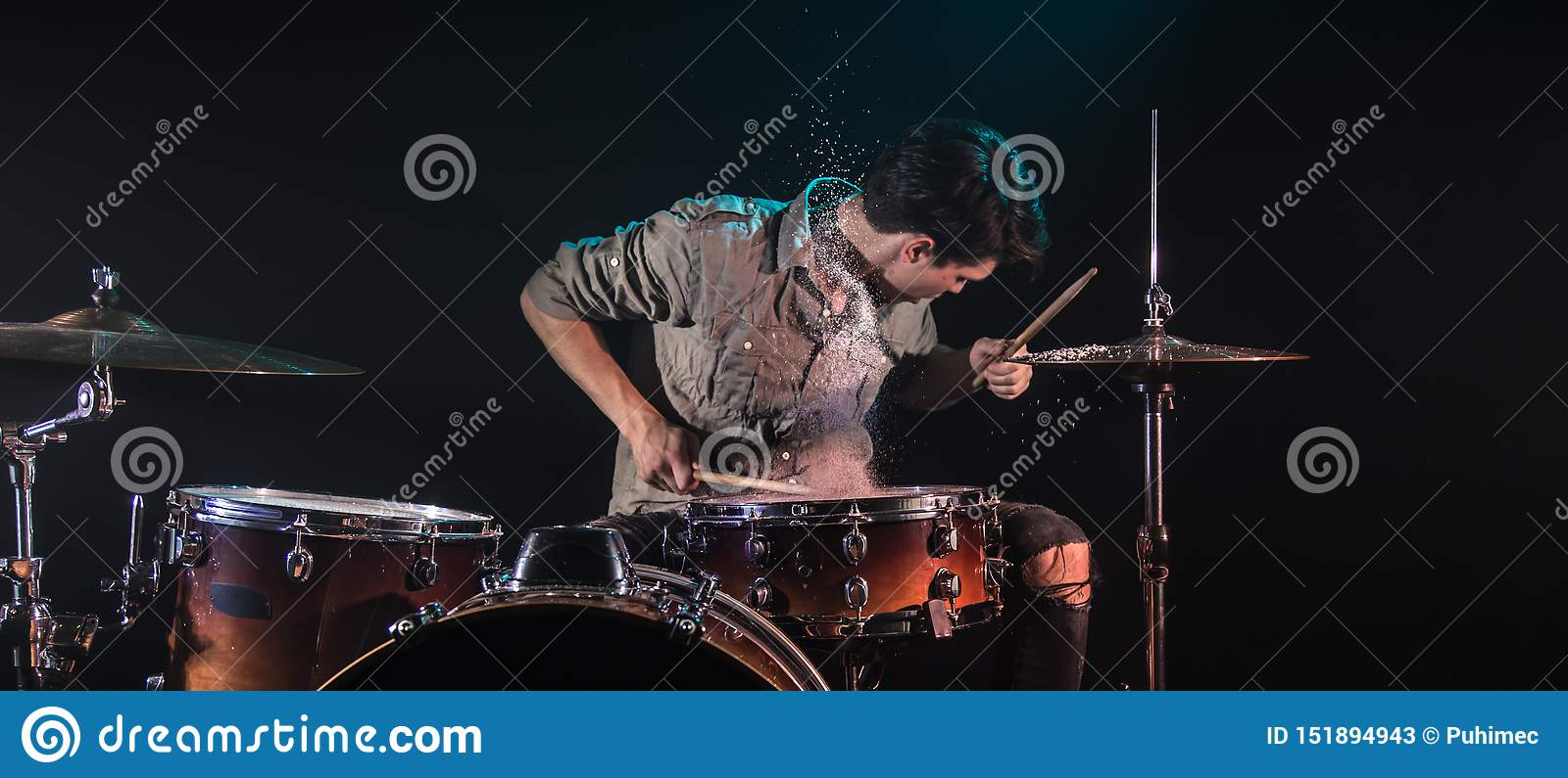 Musician playing drums with splashes, black background with beautiful soft light