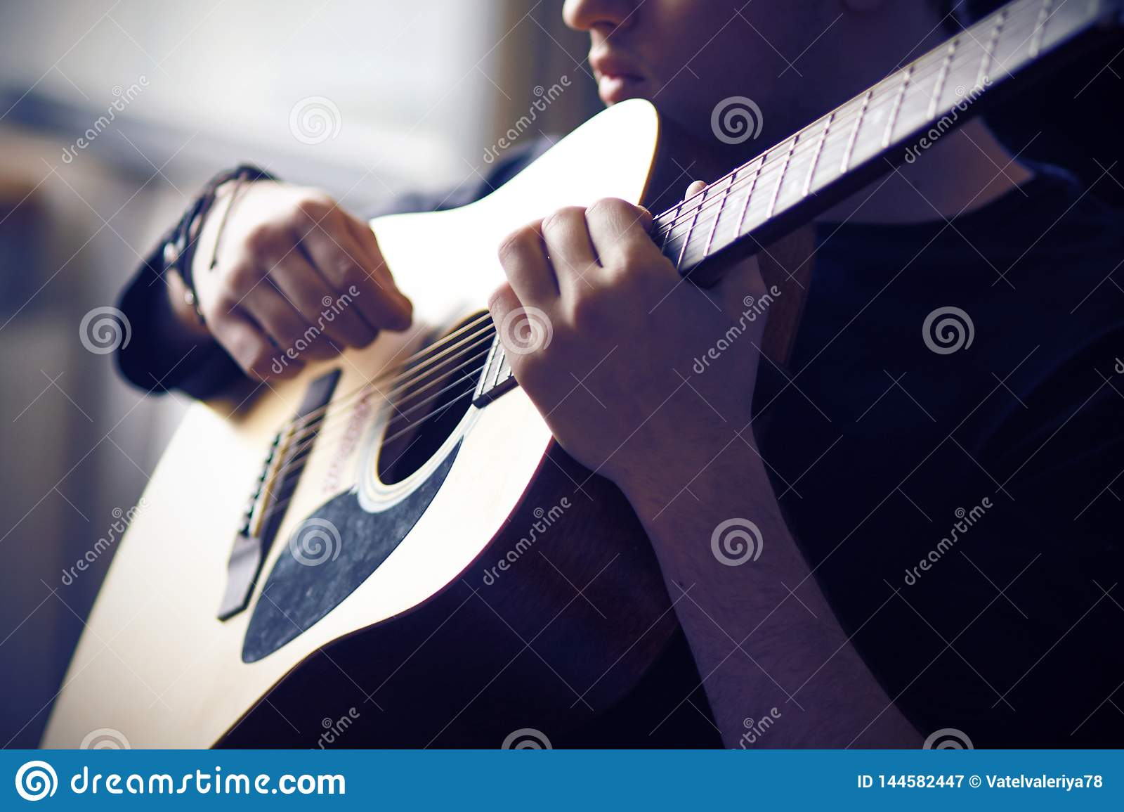 A musician plays his acoustic guitar, holding the fretboard at the base