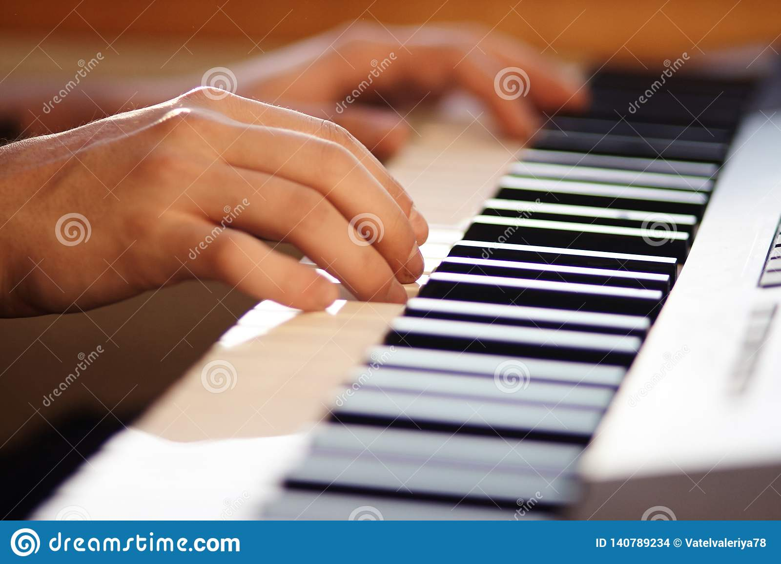 The musician pressing the keys of a modern musical synthesizer