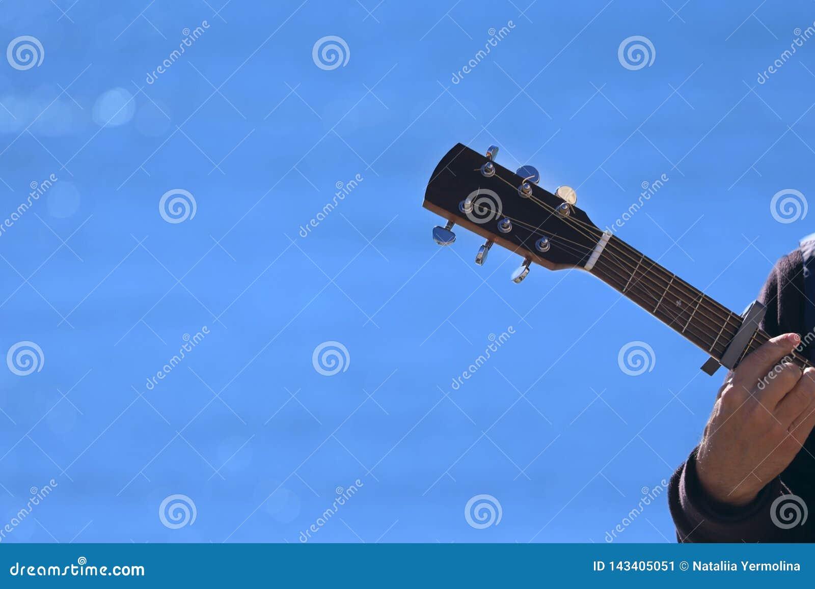 Musicien de rue Fragment de la main d un musicien sur une guitare dans la perspective de la mer bleue un jour ensoleillé