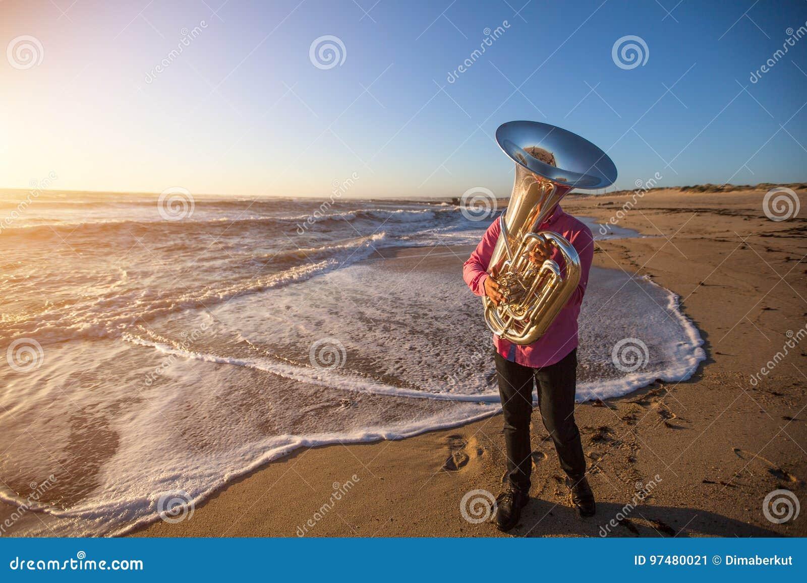 Musicista che gioca la tuba sullo strumento musicale della costa di mare