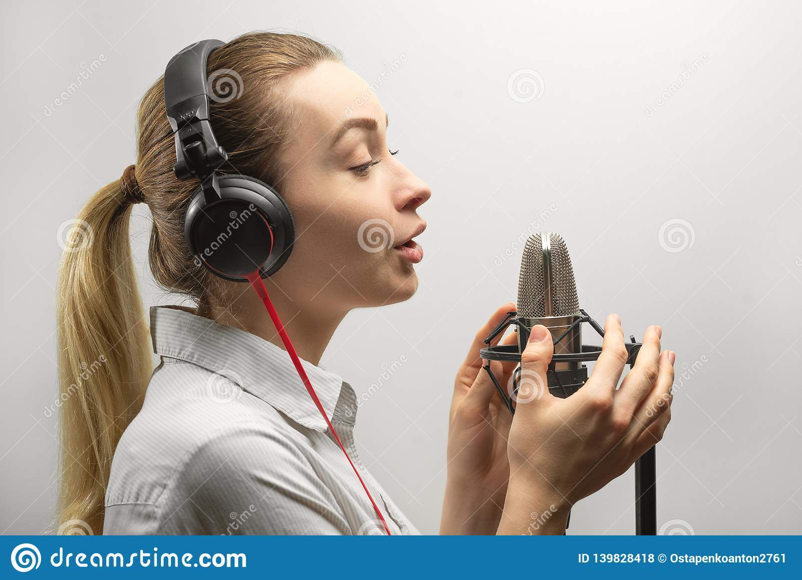 Musik, showbusiness, folk och stämmabegrepp - sångare med hörlurar och mikrofonen som sjunger en sång i inspelningstudio,