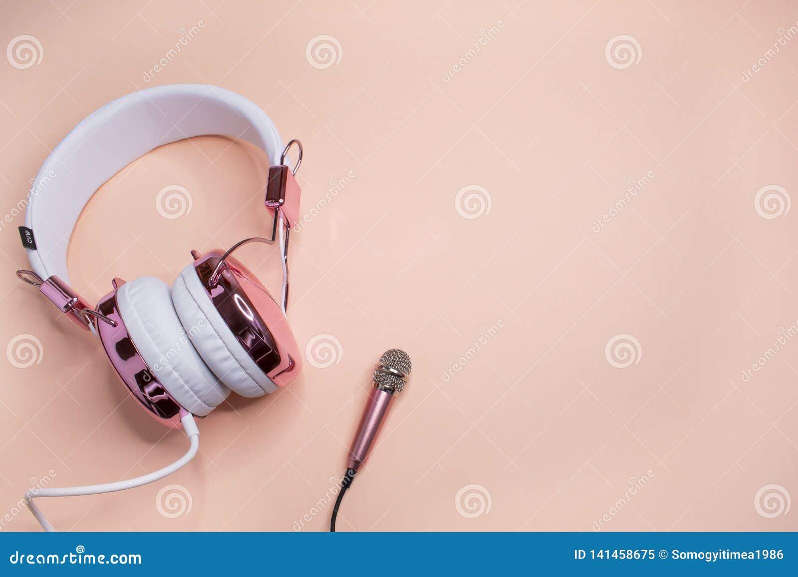 Musikhintergrund mit rosa Kopfhörern und Mikrofon