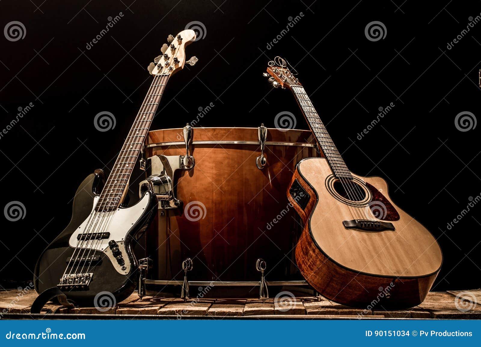 Musikinstrument, akustisk gitarr för bastrummatrumma och elbas på en svart bakgrund
