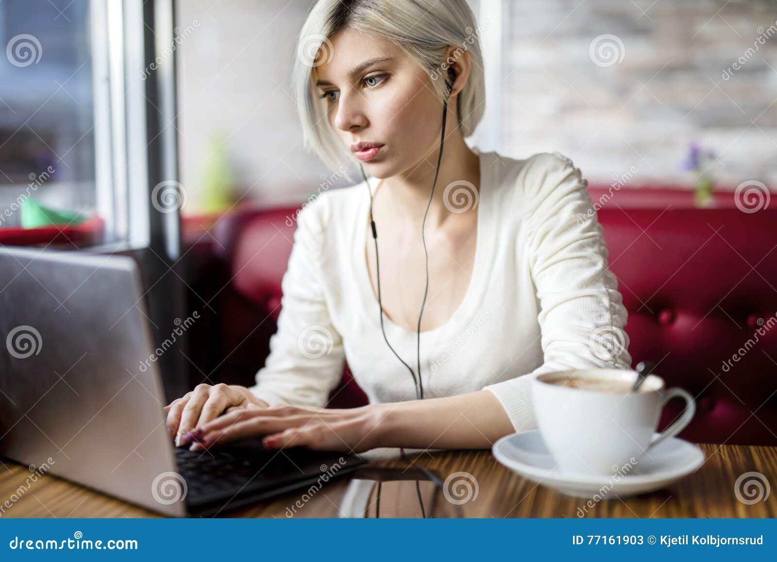 Musique de écoute de femme tout en travaillant sur l ordinateur portable en café