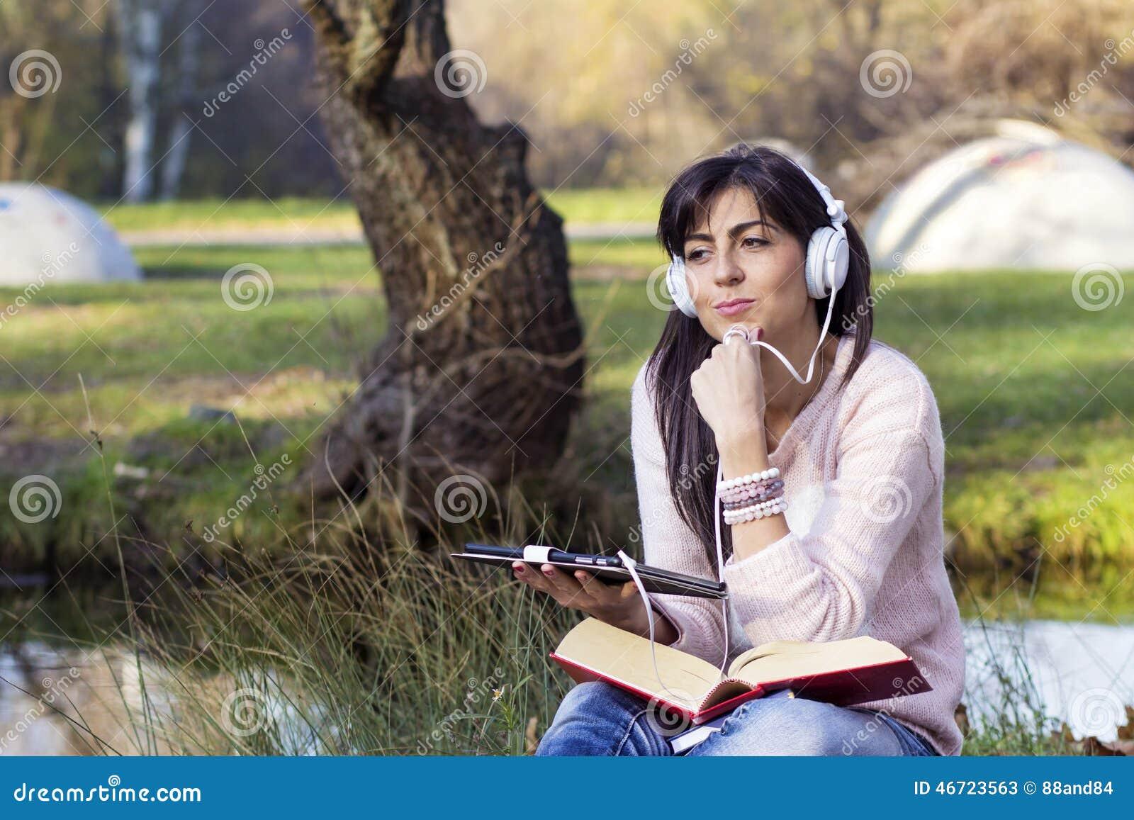 Musique de écoute de jeune femme avec son comprimé en parc d automne