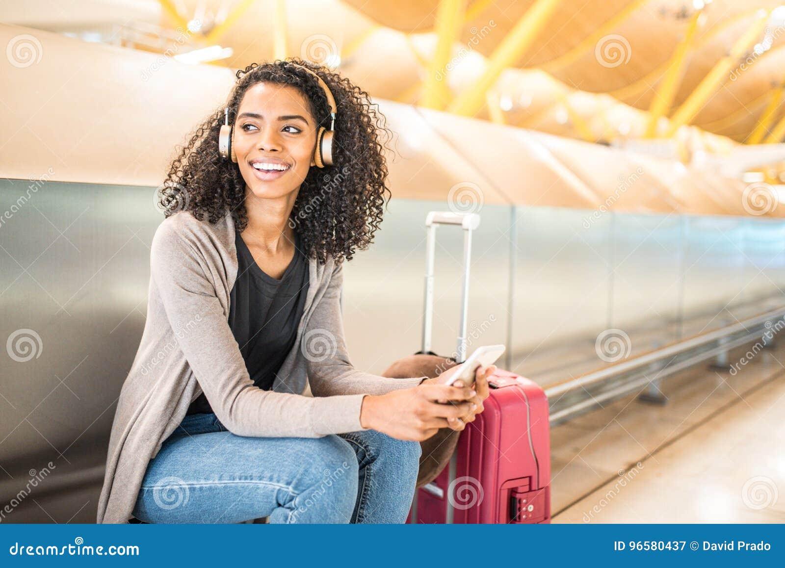 Musique de écoute de jeune femme de couleur heureuse avec des écouteurs et le mobi