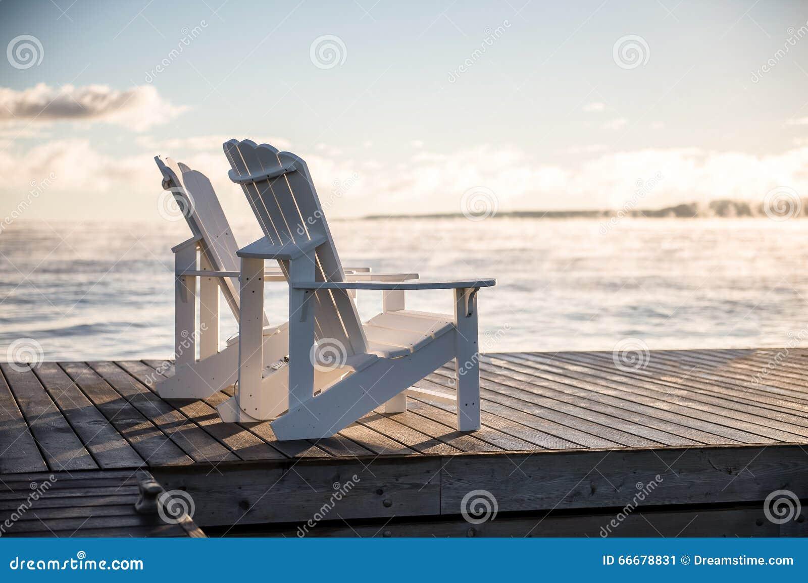 Muskoka stolar på en skeppsdocka med solresning och mist