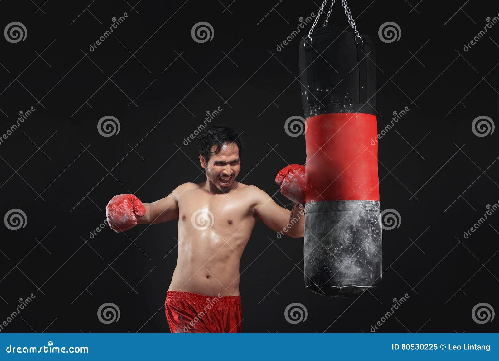Muskulös asiatisk manboxareutbildning med att stansa påsen