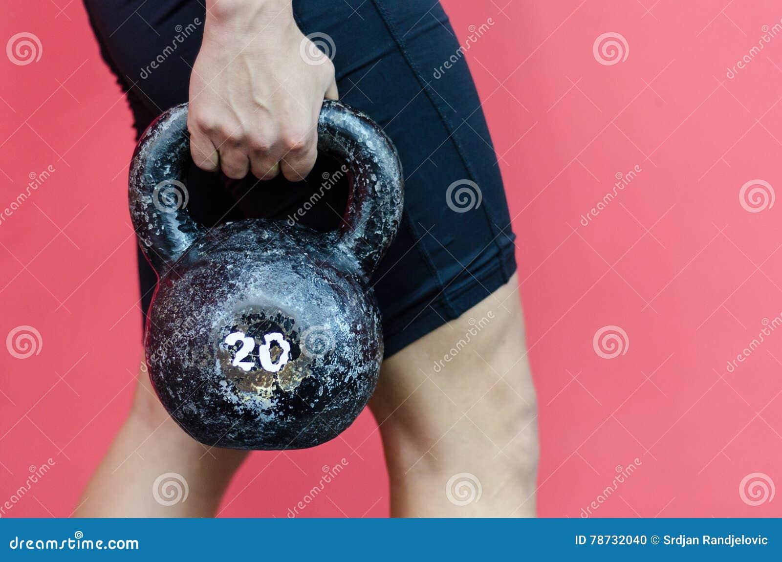 Muskulös kvinna som rymmer den gamla och rostiga kokkärlklockan