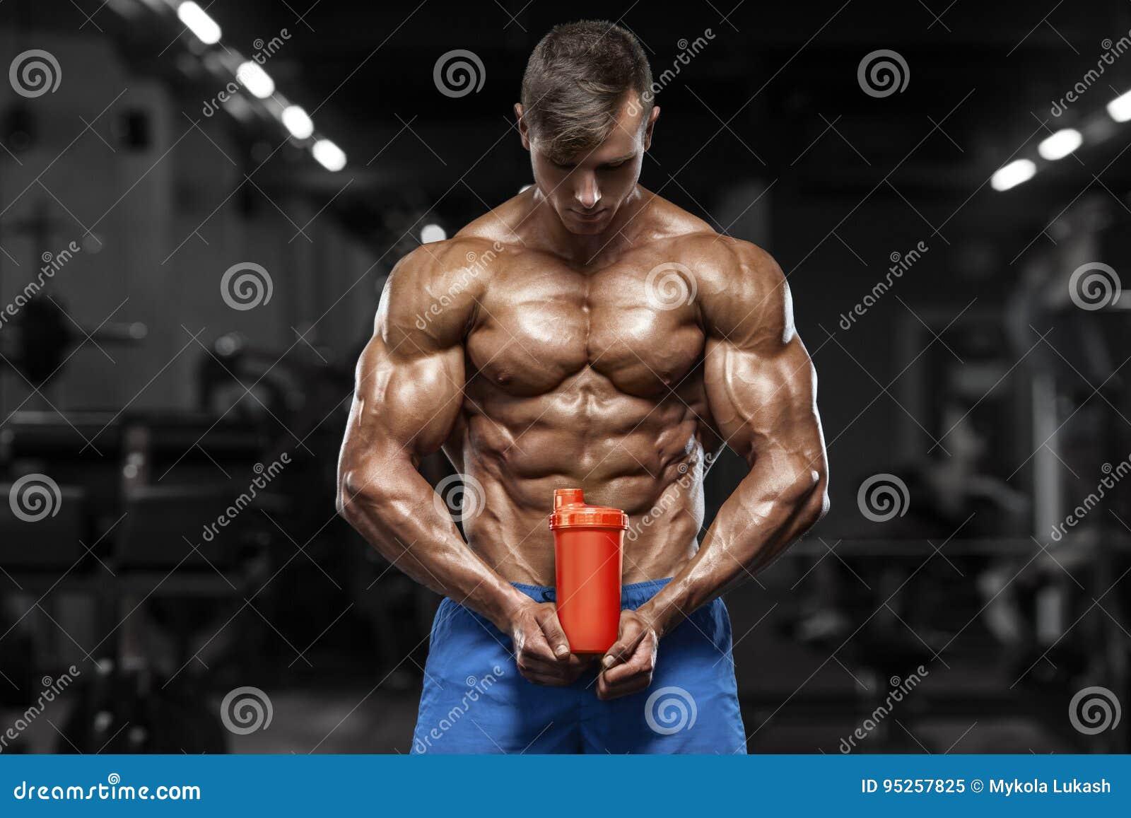 Muskulös man i idrottshallen med shaker, format buk- Stark manlig naken torsoabs som utarbetar