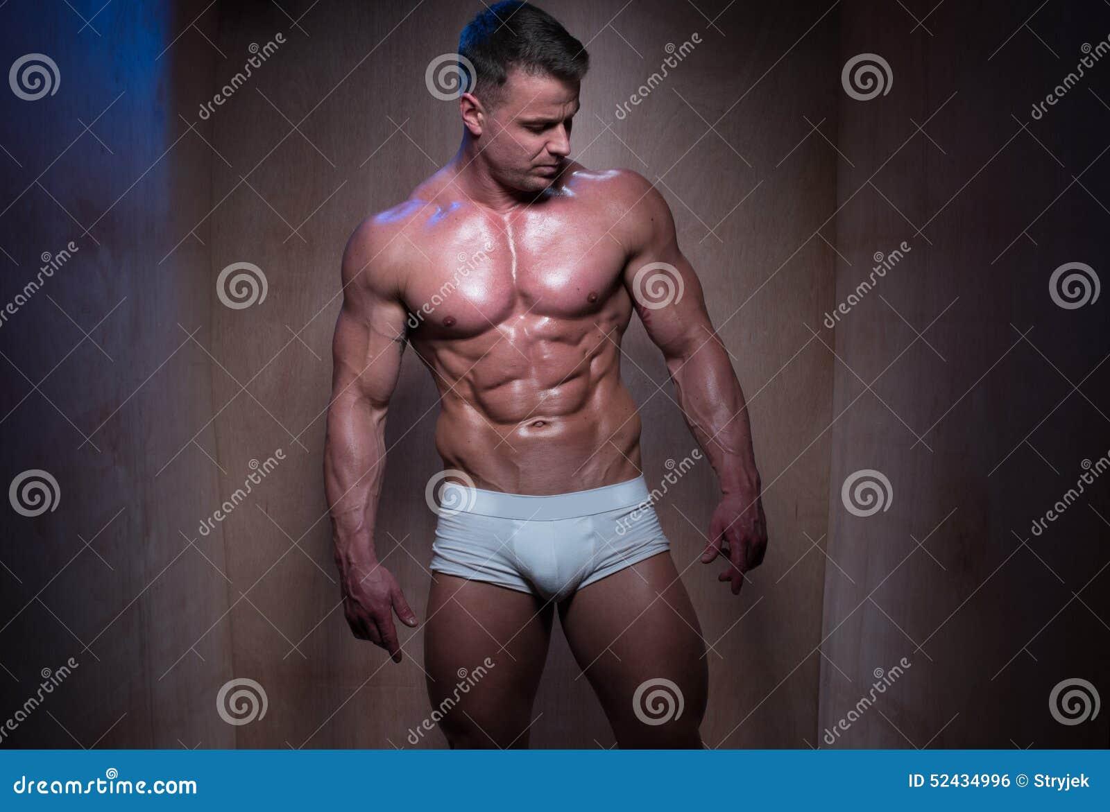 Muskulös man i vita boxarekortslutningar som ner ser