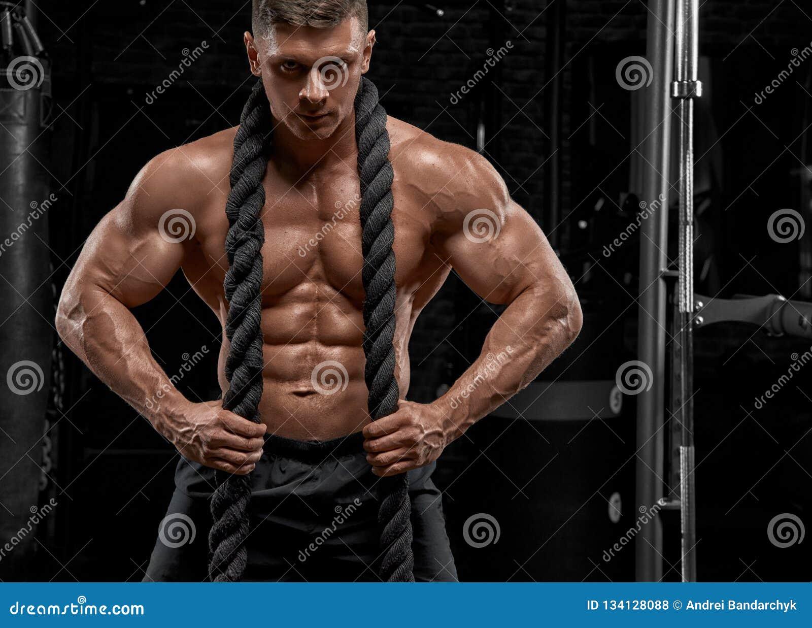 Muskulös man som utarbetar i idrottshallen som gör övningar