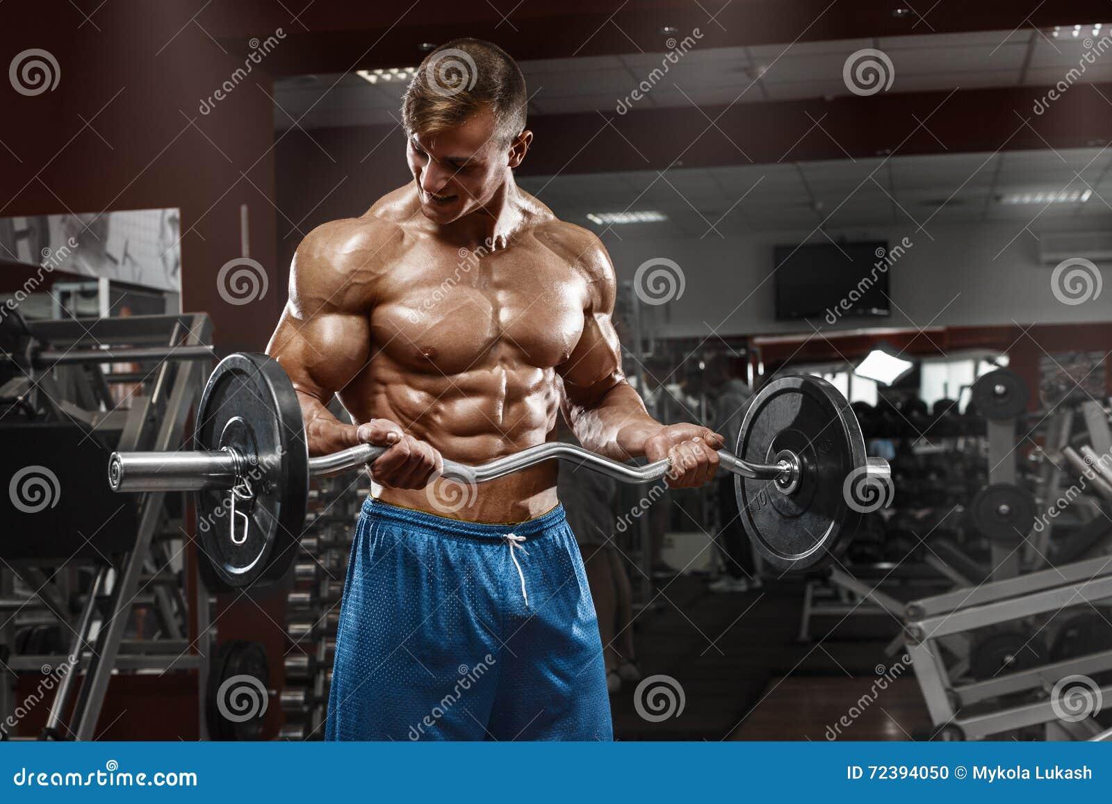 Muskulös man som utarbetar i idrottshallen som gör övningar med skivstången på biceps, manlig naken torsoabs