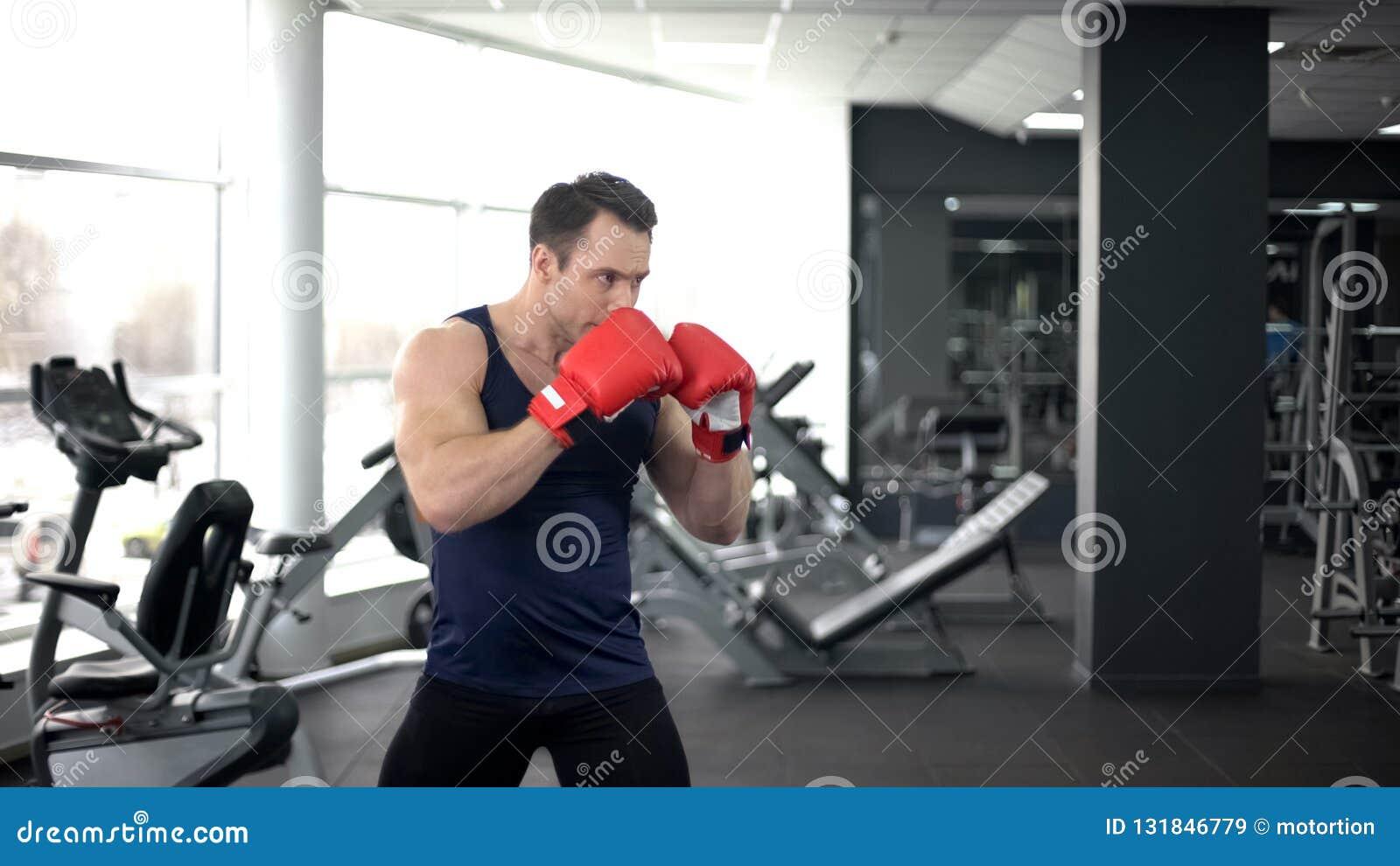 Muskulöser Boxer in den Handschuhen ausbildend in der Turnhalle, kämpfende Position tuend, Sportgeist