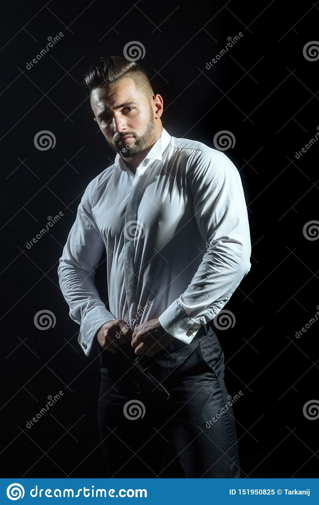 Muskulöser hübscher Kerl auf schwarzem Hintergrund wirft tragendes elegantes weißes Hemd und schwarze Hose auf Kleiderordnung für