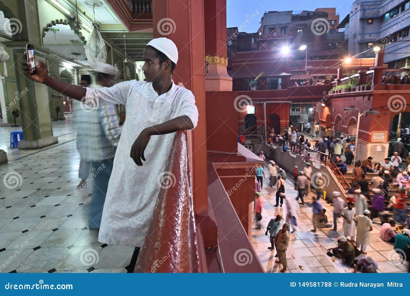 Muslim boy taking selfie during Iftar party at Nakhoda Masjid, Kolkata, India
