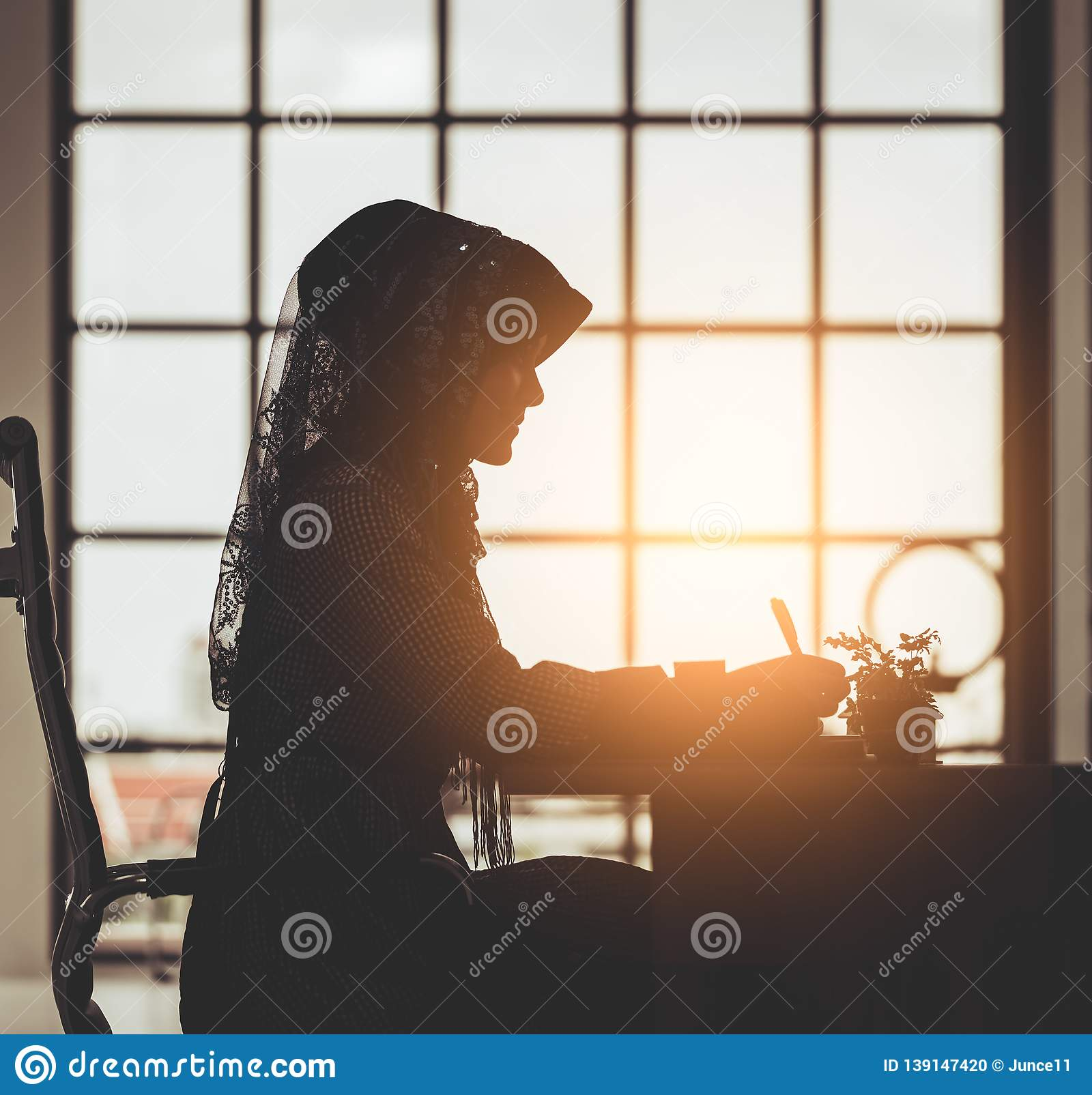 Muslim business people silhouette of islam woman working on office table windows morning flare