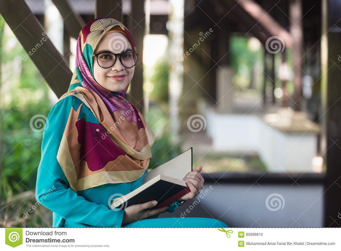 Muslim girl with glasses and veil holding opened book at park a muslim girl with