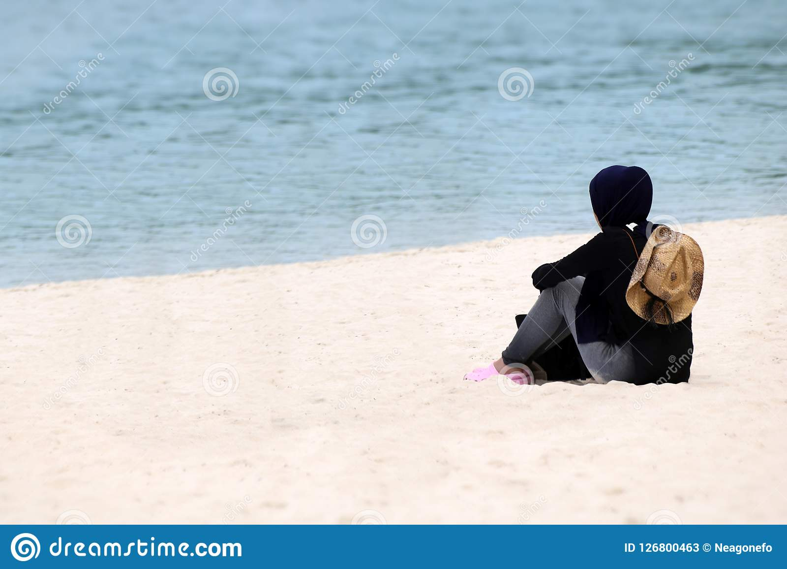 Muslim girl traveler on hijab sitting on the beach