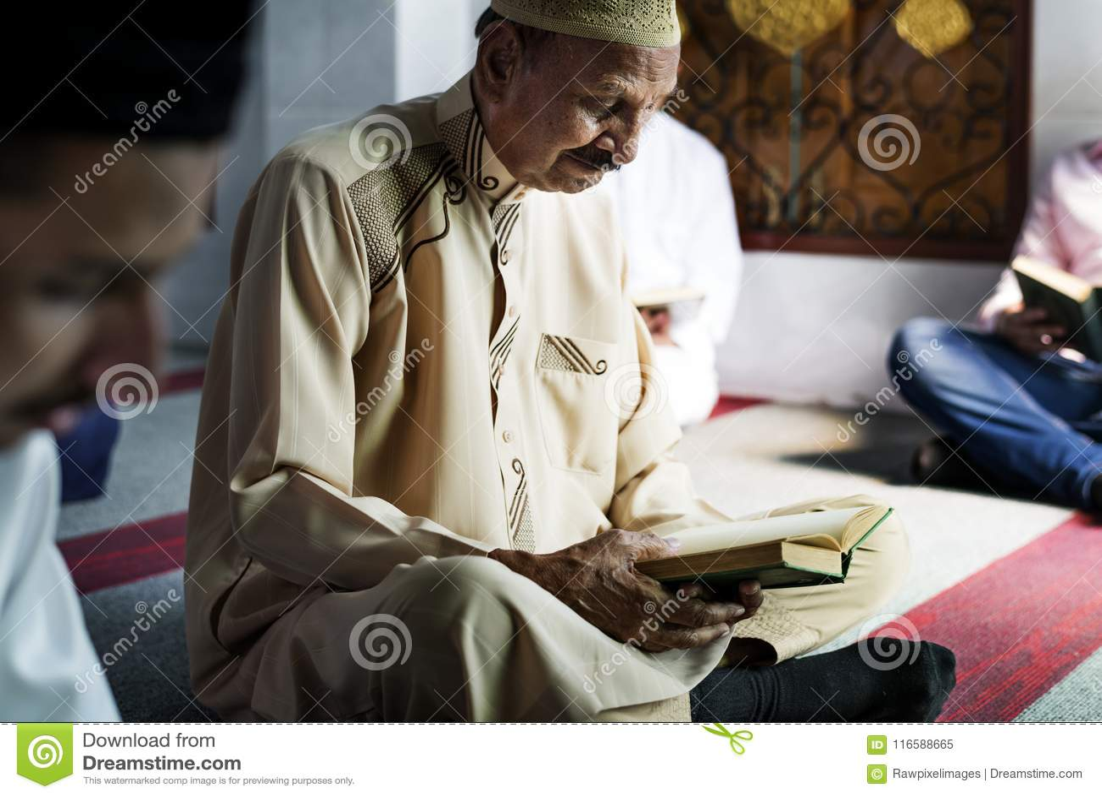 Muslim men reading Quran during Ramadan