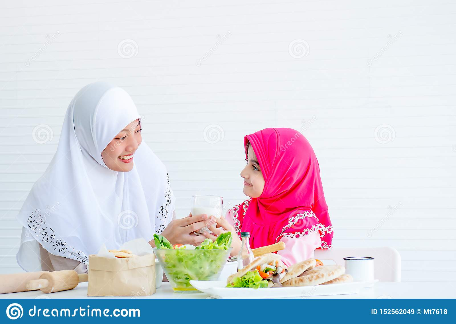 Muslim mother serve glass of milk to her little girl and also look to each other with smiling, bowl of vegetable salad on the
