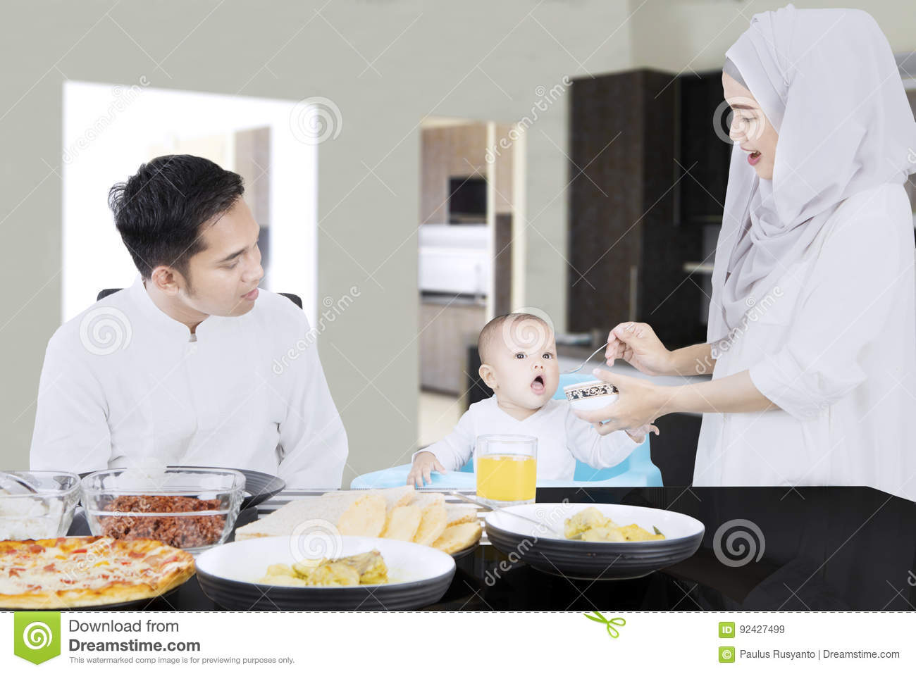 Young muslim women feeding her baby on a high chair with her husband in the  dining room at home a61e586020