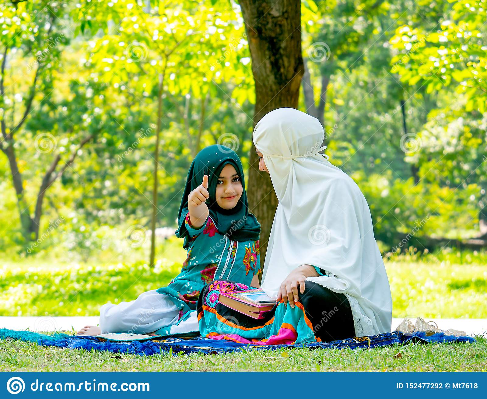 Muslim woman look at her child and girl show thumps up to the camera during reading some books in the garden