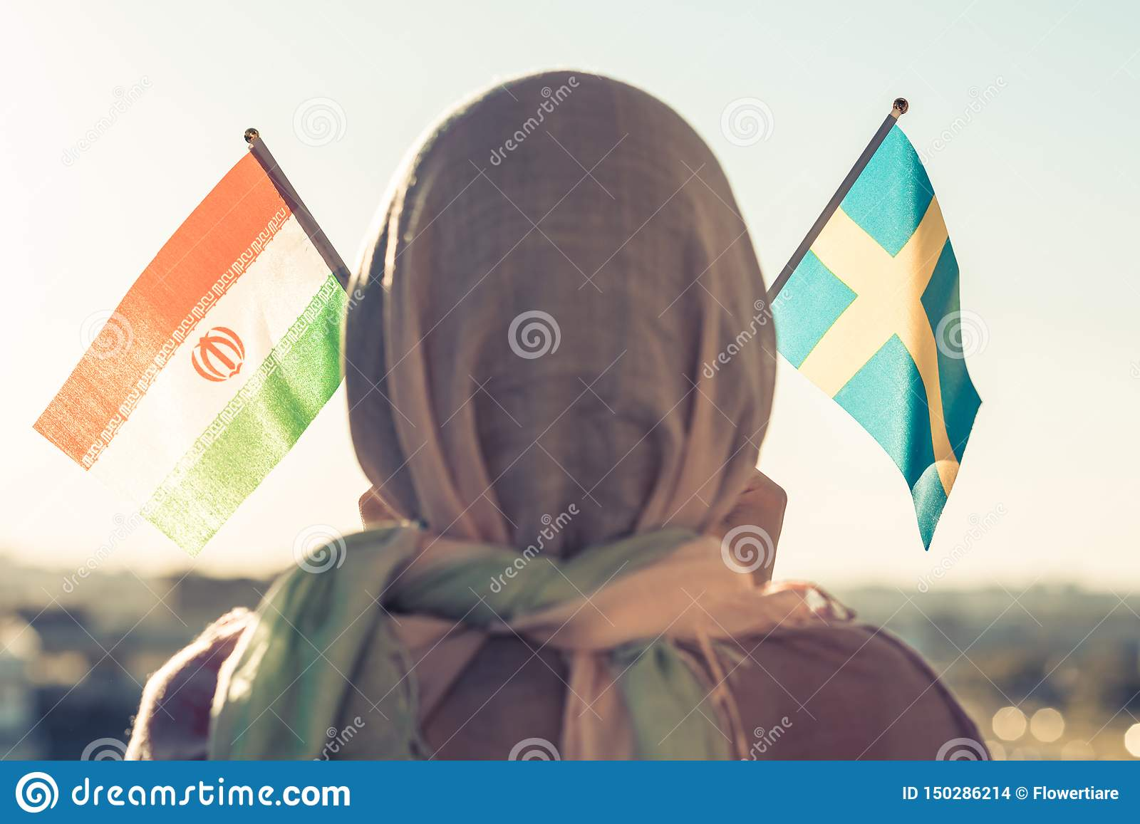 Muslim woman in scarf with Swedish and Iranian flags of at sunset.Concept.