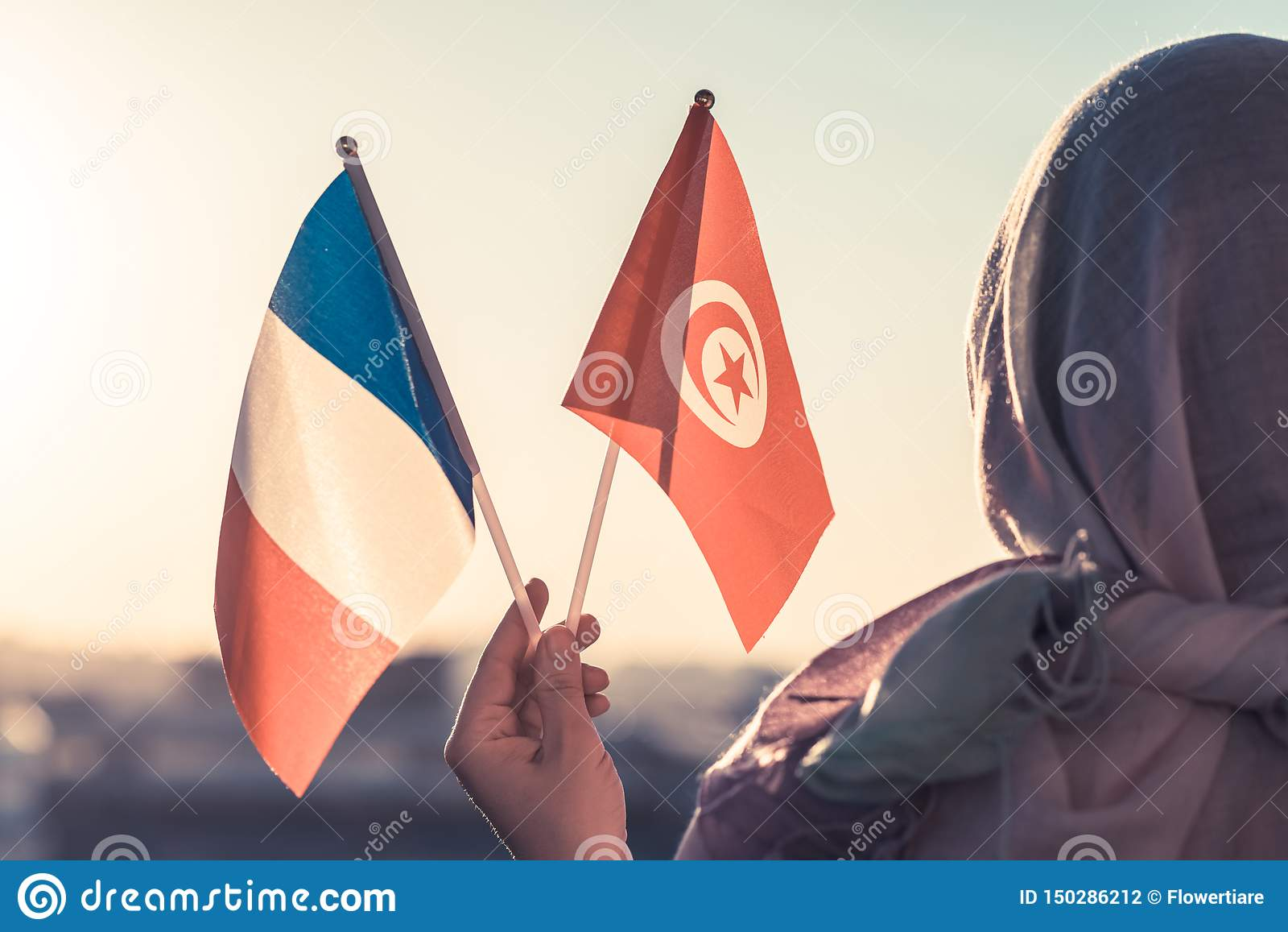 Muslim woman in scarf with Tunisia and French flags of at sunset.Concept.