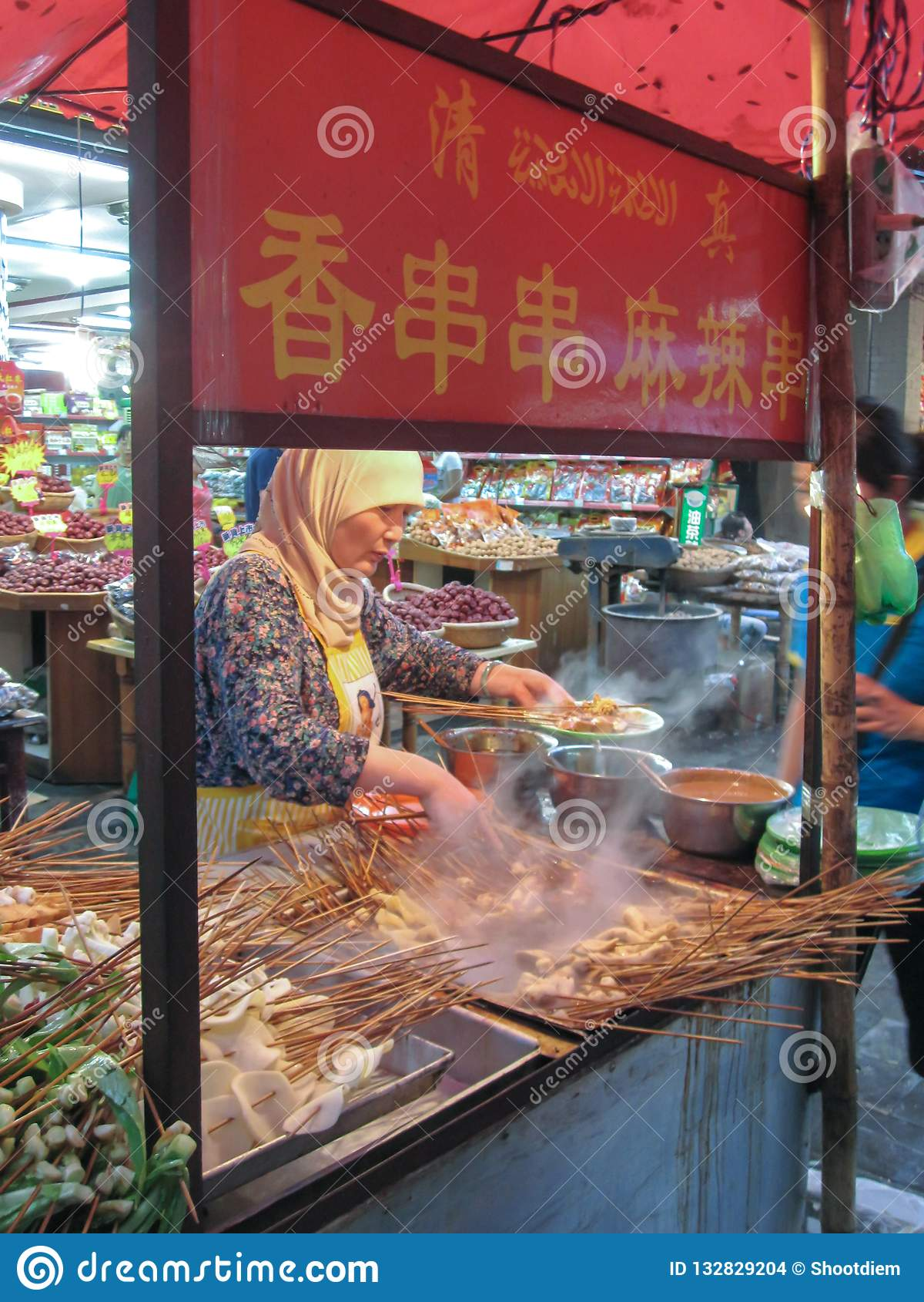 Muslimsk kines från den Hui person som tillhör en etnisk minoritet som lagar mat buntar av köttsteknålar på Beiyuanmen den muslim