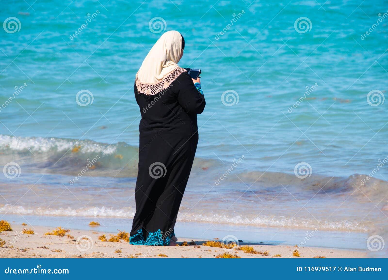 Muslimsk kvinna i svart ämbetsdräkt och halsduken för vit som head ser hennes c