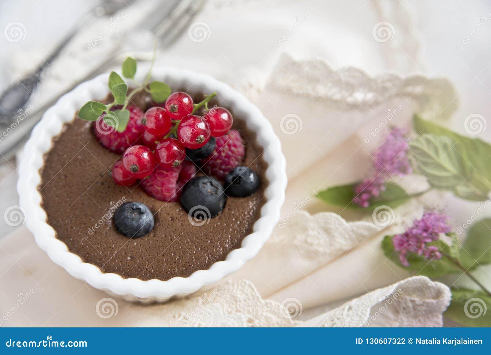 Musse de chocolate com bagas em um guardanapo claro e uma colher e uma forquilha velhas