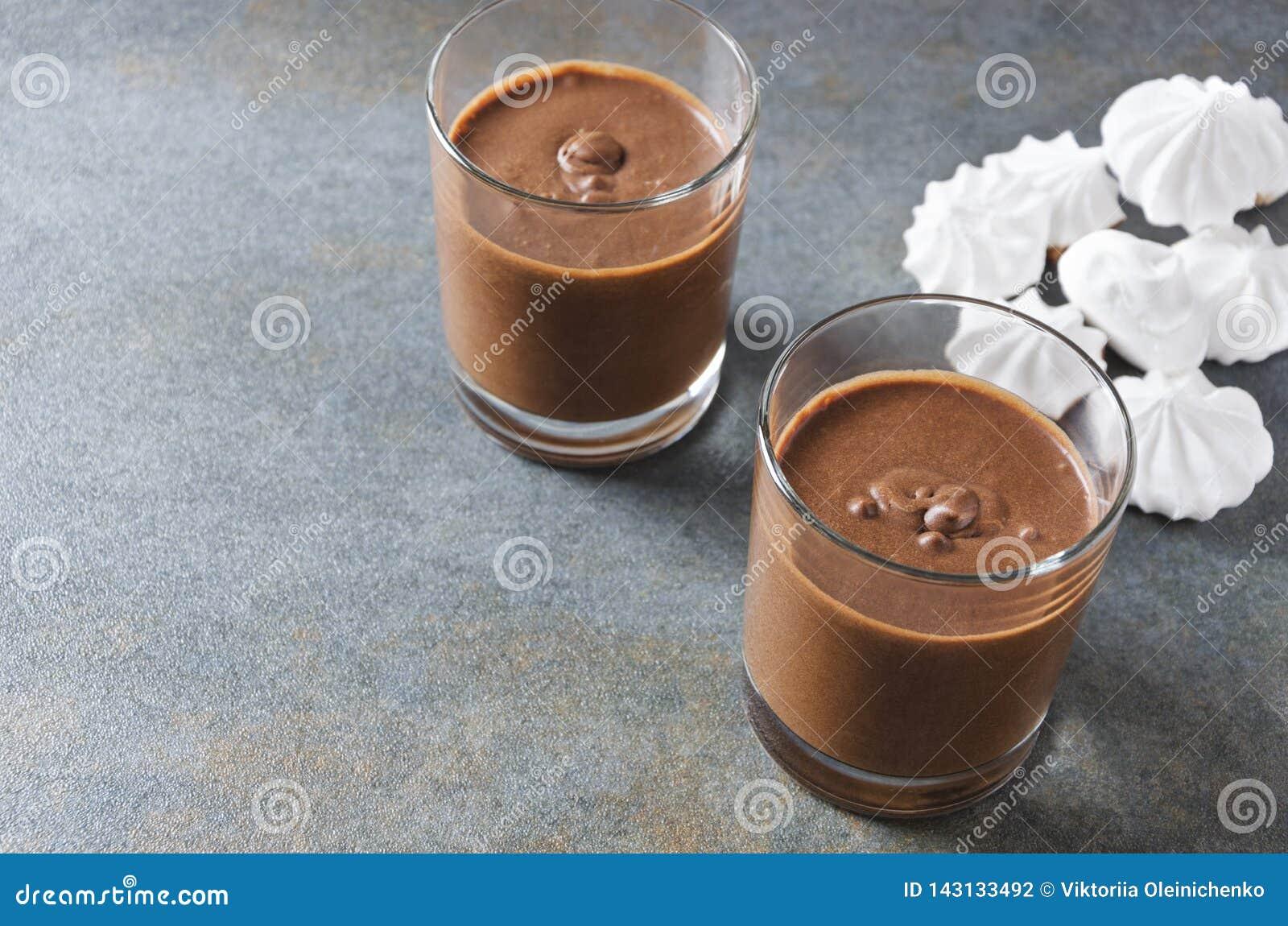 Musse saboroso com chocolate Dois copos de vidro completamente do rato do chocolate na tabela rústica cinzenta Espaço vazio para