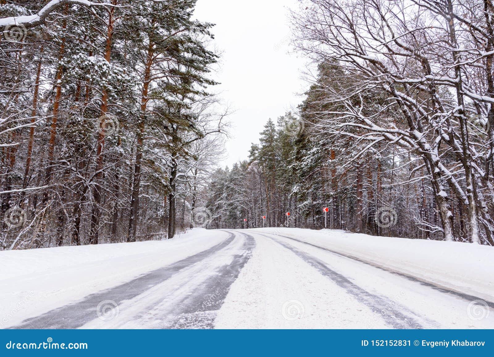 Muster auf der Winterlandstraße in Form von vier Geraden Snowy-Straße auf dem Hintergrund des schneebedeckten Waldes