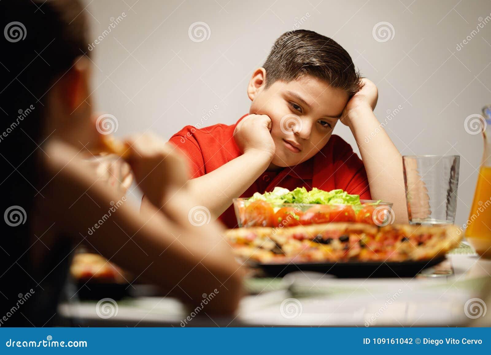 Mutter, die dem überladenen Sohn Salat anstelle der Pizza gibt