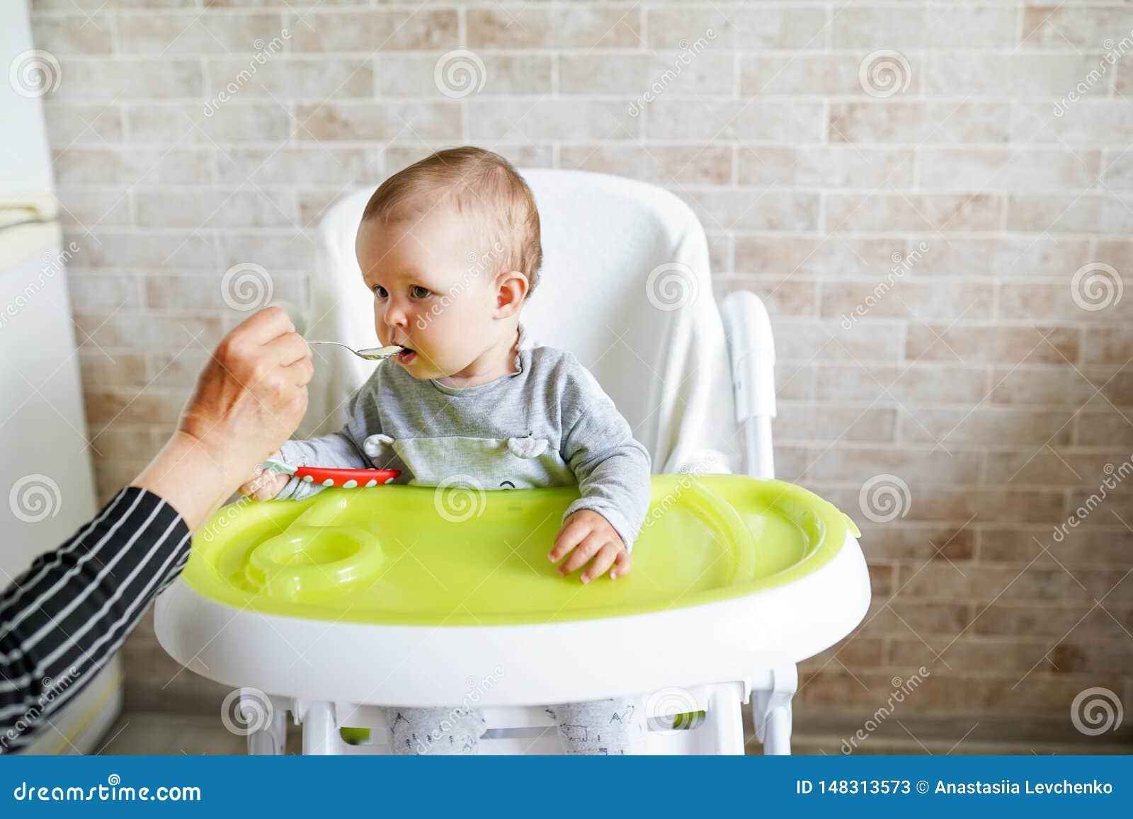 Mutter, die ihr Baby mit einem L?ffel, Kind isst in der sonnigen K?che einzieht Kopieren Sie Platz