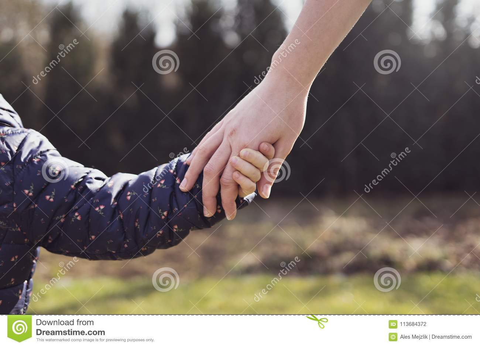 Mutter, die ihre Tochterhand hält
