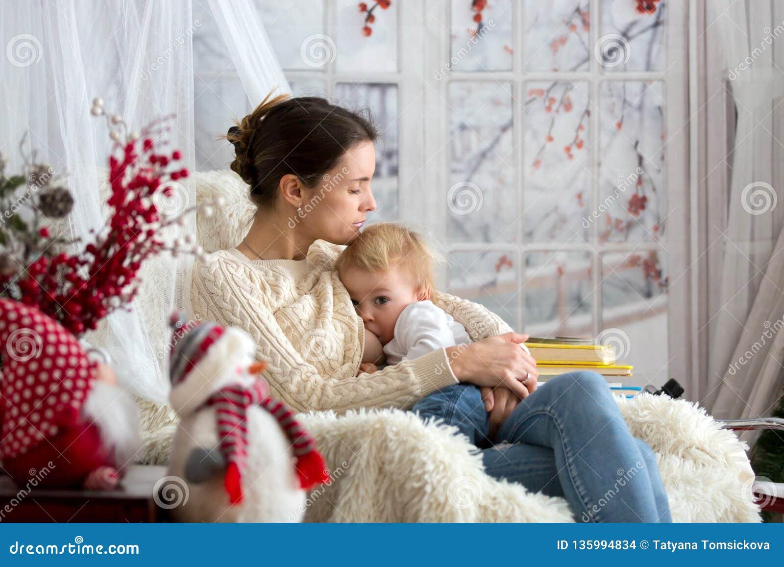 Mutter, die ihren Kleinkindsohn sitzt im gemütlichen Lehnsessel, Winterzeit stillt