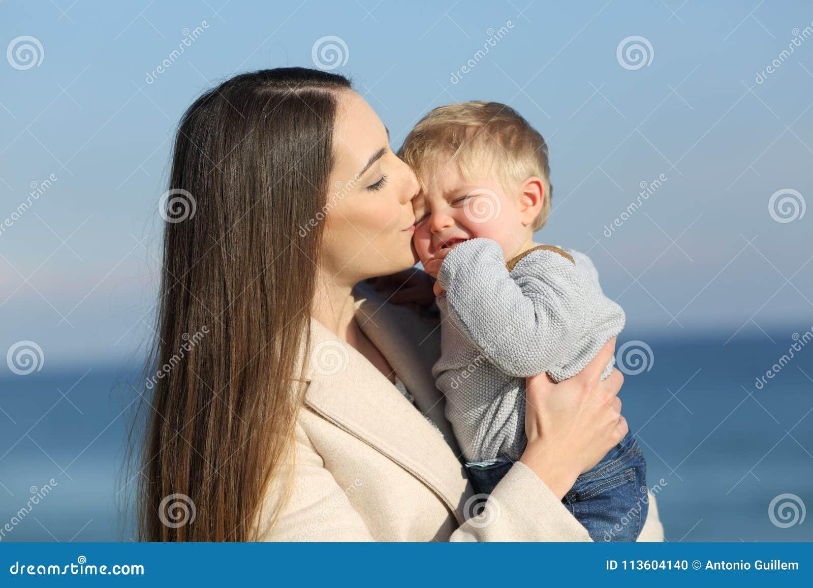 Mutter, die ihren verärgerten Sohn küsst