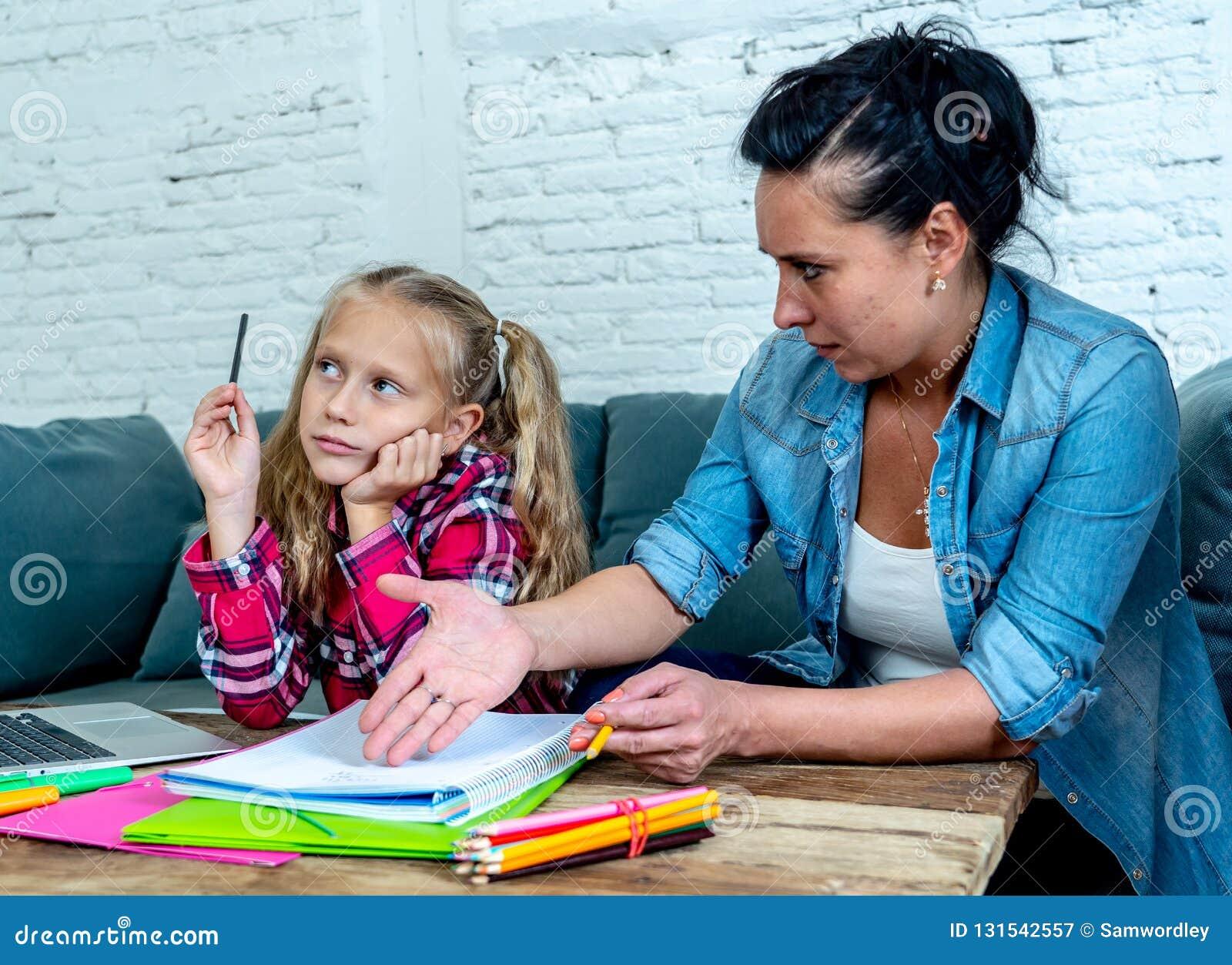 Mutter, die mit Tochter frustriert wird, während, die Hausarbeit tuend, die zu Hause auf Sofa bei der Lernschwierigkeitenhausarbe