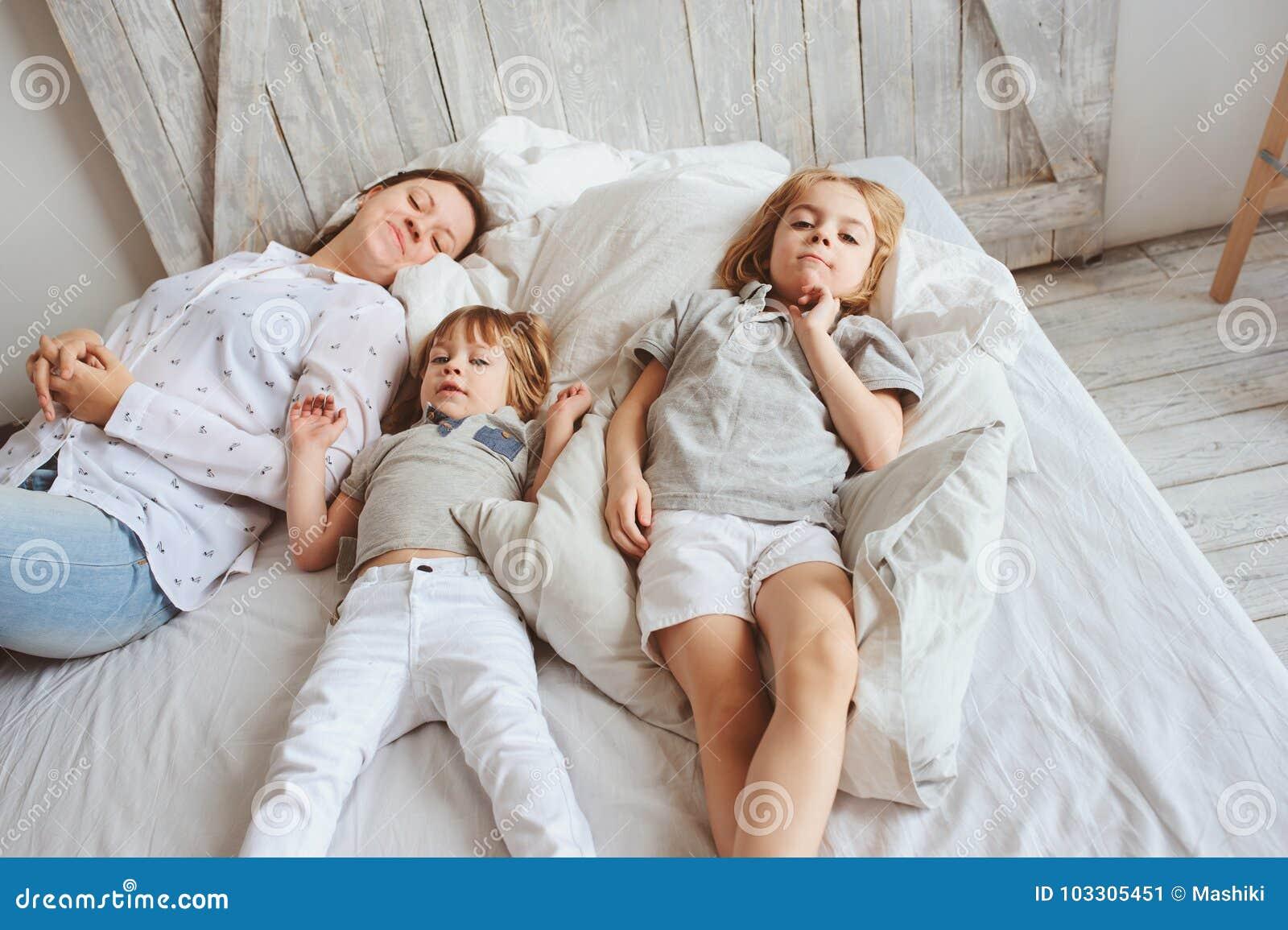Mutter, die morgens mit Geschwister auf Bett spielt Glückliche Familie mit zwei Kinderjungen
