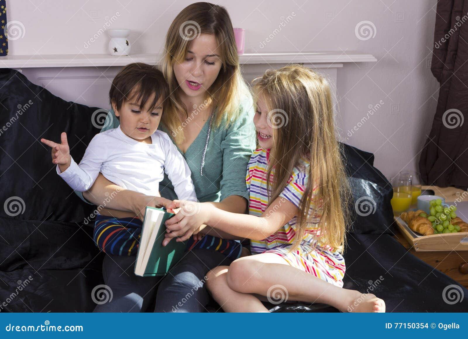 Mutter, die zu den Kindern im Bett liest